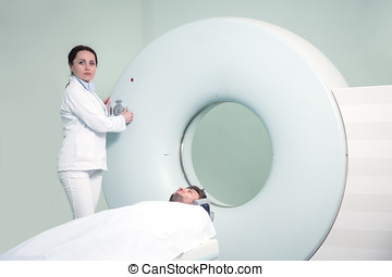 Mid adult nurse preparing patient for CT scan test in hospital room