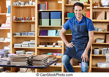 Mid Adult Salesman Sitting On Ladder In Book Store -...