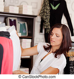 Mid adult saleswoman Examining Clothes On Mannequin -...