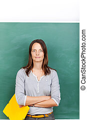 Mid Adult Teacher Holding File Against Chalkboard