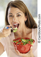 Mid Adult Woman Eating A Fresh Green Salad