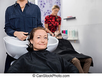 Mid Adult Woman Getting Hair Washed In Salon