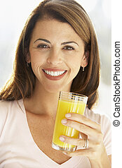 Mid Adult Woman Holding A Glass Of Orange Juice, Smiling At The Camera