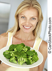 Mid Adult Woman Holding A Plate Of Broccoli