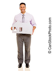 mid age businessman holding paper house