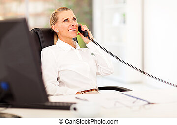 mid age businesswoman talking on the phone in office