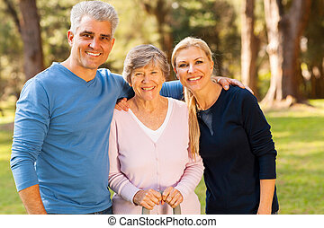 mid age couple and senior mother outdoors - loving mid age...