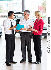 mid age couple buying a new car at dealership