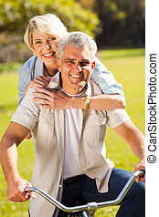 mid age couple on one bike outdoors