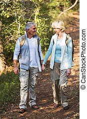 mid age couple walking in the forest