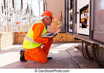 mid age electrician kneeing in front of transformer -...
