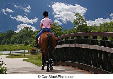 mid-age female horse ridder crossing bridge