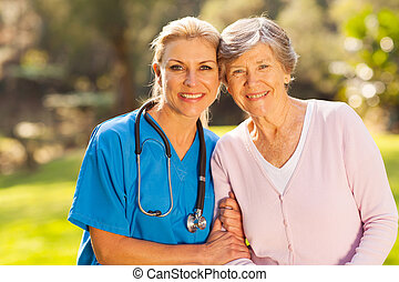 medical nurse and senior patient outdoors - mid age medical...