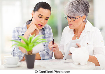 mid age mother helping daughter with her financial at home