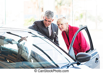 mid age salesman showing new car to customer