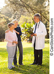 mid age woman and senior mother talking to doctor