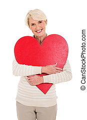 mid age woman hugging red heart shape - beautiful mid age...