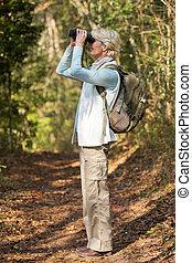 mid age woman using binoculars bird watching - side view of...