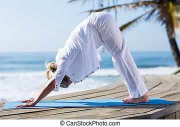 mid age woman yoga exercise on beach - healthy mid age woman...