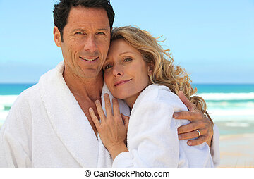 mid aged couple wearing a bathrobe near the sea