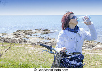Mid aged woman biker drinks water