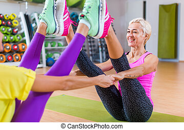 Mid-aged woman working out in pairs on mats in a gym. in sportswear doing yoga buddy boat pose with partner