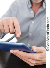 Mid section of a businessman using digital tablet at table -...