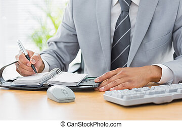 Mid section of a businessman writing in diary