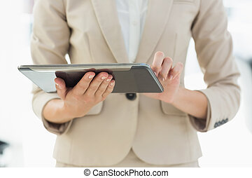 Mid section of a businesswoman using digital tablet