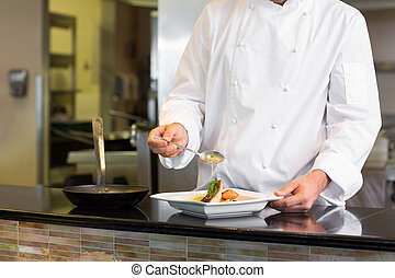 Mid section of a chef garnishing food in kitchen