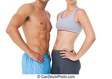 Mid section of a fit young couple standing over white ...