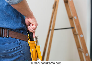 Mid section of a handyman with toolbelt