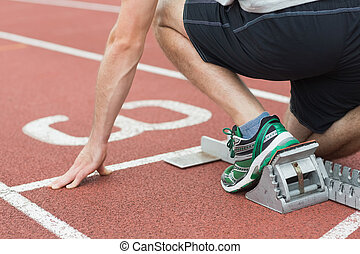 Mid section of a man ready to race on running track -...