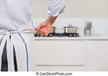 Mid section of a man wearing apron in kitchen