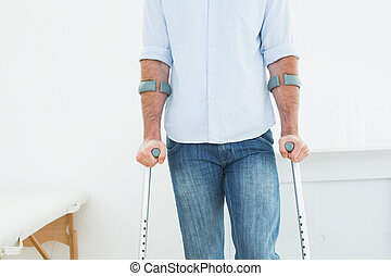 Mid section of a man with crutches in medical office
