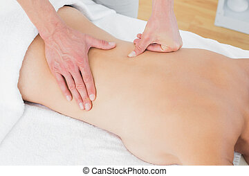 Mid section of a physiotherapist massaging woman's back - ...
