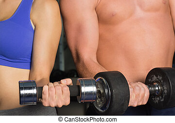 Mid section of a shirtless man and woman with dumbbells