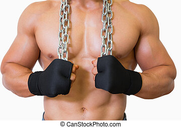 Mid section of a shirtless muscular man holding chain