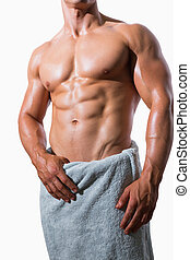 Mid section of a shirtless muscular man in white towel over...
