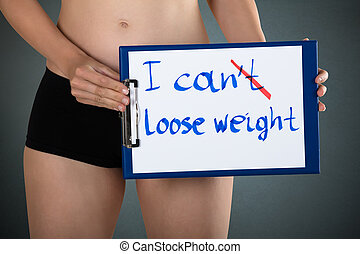 Woman Showing Message I Can't Lose Weight - Mid Section Of A...