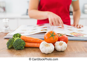 Mid section of a woman with recipe book and vegetables