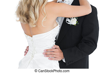 Mid section of a young dancing married couple on white...