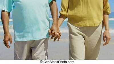 Mid section of active senior African American couple holding hands and walking on the beach 4k