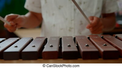 Mid section of Asian schoolboy playing xylophone in a ...