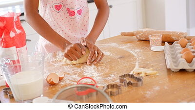 Mid section of black girl kneading dough on worktop in kitchen of comfortable home 4k