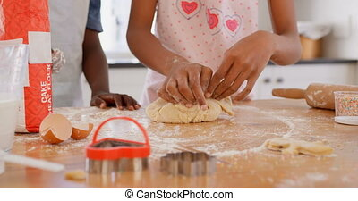 Mid section of black girl kneading dough on worktop in ...