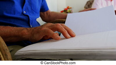 Mid section of blind senior man reading a braille book at ...