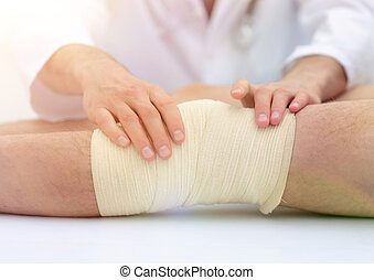 Mid section of doctor bandaging leg of patient in hospital