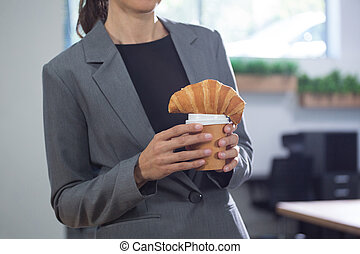 Mid section of female executive holding coffee and croissant