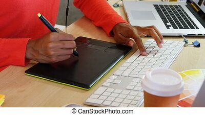 Mid section of female fashion designer using graphic tablet at desk in office 4k